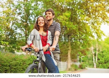 people in love - riding together on the same bicycle - stock photo