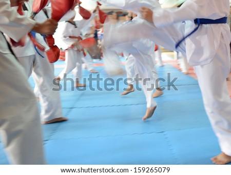 People in martial arts training exercising Taekwondo. blur motion - stock photo