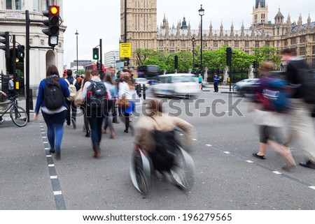 people in motion blur crossing the street near Big Ben and Westminster Palace in London - stock photo