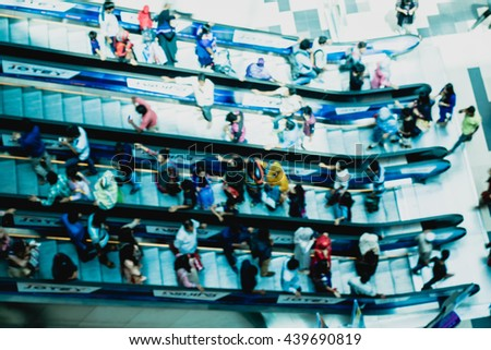 People in motion blur in escalators at the modern shopping mall - stock photo