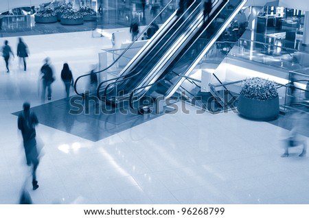 People in motion in escalators at the shopping mall - stock photo
