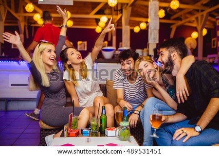 People in night club dancing, drinking and having fun