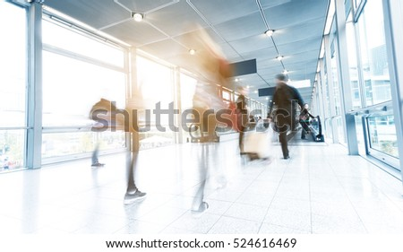 people in rush on a traidshow corridor