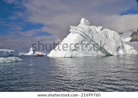 People in small zodiac exploring big iceberg - stock photo