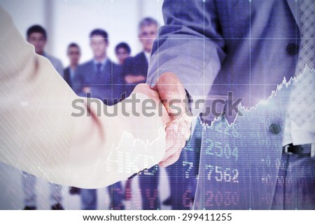 People in suit shaking hands against stocks and shares - stock photo