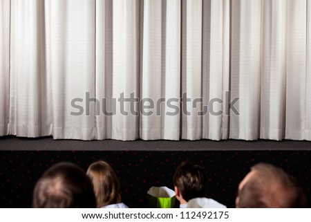 People in the cinema waiting for the movie to start - stock photo