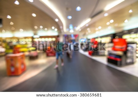 People in the duty free shop at the airport. Blur effect. - stock photo