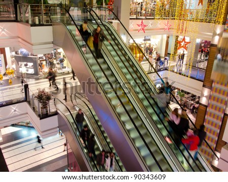 People in the multilevel mall, motion blurred - stock photo