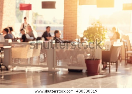 People in the restaurant. Blurred effect applied. - stock photo