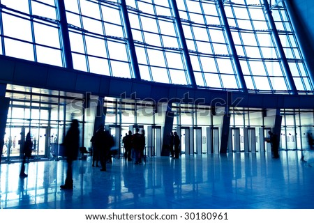 People in wide blue enter hall window in exposition center, left copmosition - stock photo