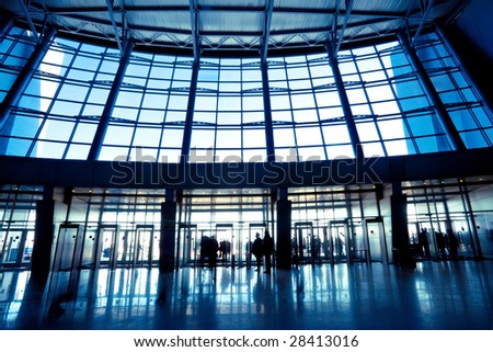 People in wide blue hall window in exposition center - stock photo