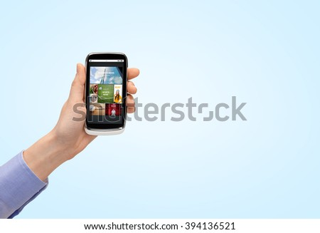 people, internet, technology and media concept - close up of woman hand with smartphone with web pages on screen
