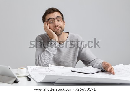 people bored at work. people, job, tiresome and overwork concept. bored sleepy male engineer working on blueprints people at work