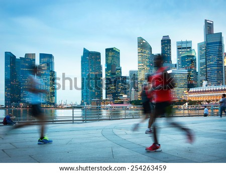 People jogging at dusk in Singapore. Singapore Downtown Core in the background - stock photo