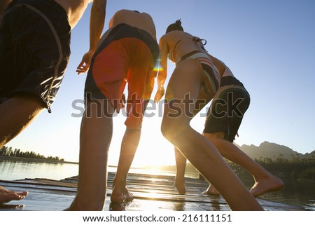 People jumping off dock into lake - stock photo