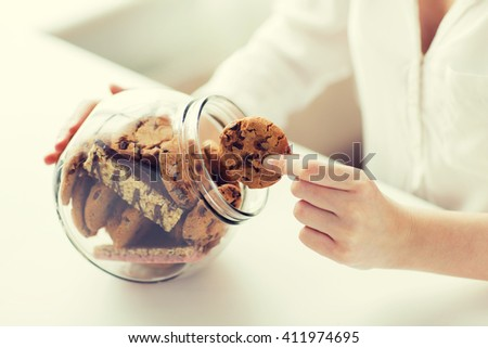 people, junk food, culinary, baking and unhealthy eating concept - close up of hands with chocolate oatmeal cookies and muesli bars in glass jar - stock photo