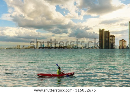 People kayaking in the ocean, man who try reach for the shore - stock photo