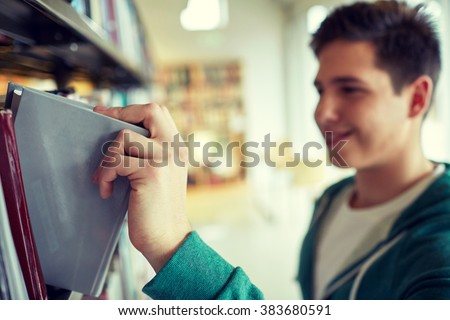 people, knowledge, education and school concept - close up of happy student boy or young man taking book from shelf in library - stock photo