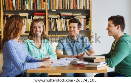 people, knowledge, education and school concept - group of happy students with books talking and preparing to exam in library - stock photo