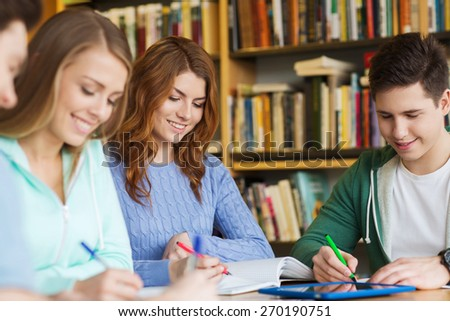 people, knowledge, education and school concept - group of happy students with tablet pc computer writing to notebooks in library