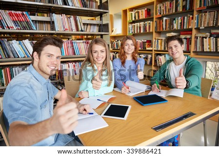 people, knowledge, education and school concept - group of happy students with tablet pc computers showing thumbs up in library - stock photo