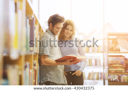 people, knowledge, education and school concept - happy student couple with books in library - stock photo