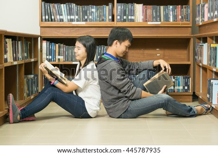 people, knowledge, education and school concept - happy student  with book in library