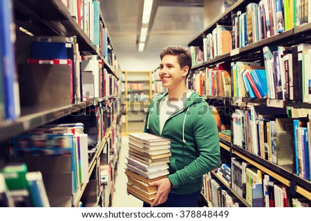 people, knowledge, education, literature and school concept - happy student or young man with book in library - stock photo