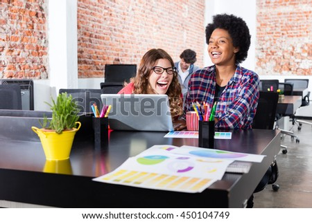 People laughing sitting office desk laptop colleagues fun joke business woman casual wear together  - stock photo