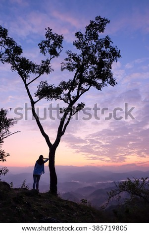 people leaning against a tree - stock photo