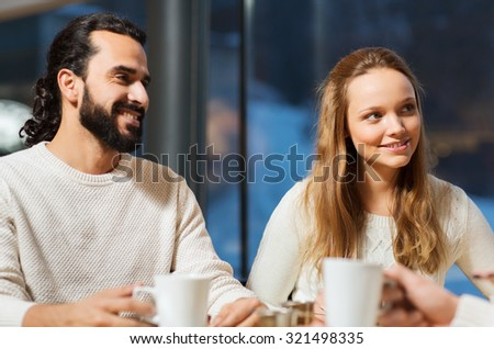 people, leisure and communication concept - happy friends or couple meeting and drinking tea or coffee at cafe - stock photo