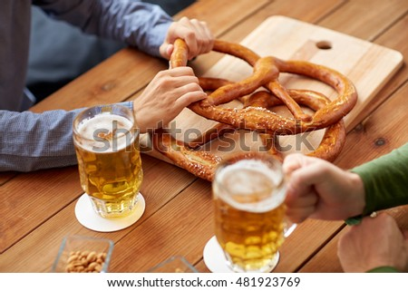 people, leisure and drinks concept - close up of men drinking beer with pretzels at bar or pub