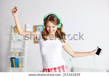 people, leisure and technology concept - happy woman or teenage girl in headphones listening to music from smartphone and dancing on bed at home - stock photo
