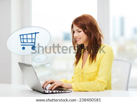 people, leisure and technology concept - smiling young woman with laptop computer and trolley icon shopping online at home - stock photo