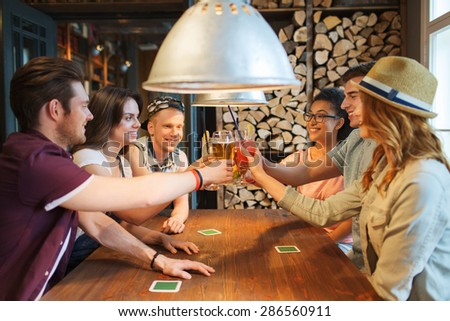 people, leisure, celebration and party concept - group of happy smiling friends clinking glasses with drinks at bar or pub - stock photo