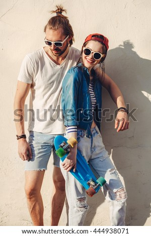 people, leisure, communication and sport concept - happy teenage friends with longboard hugging on city street - stock photo