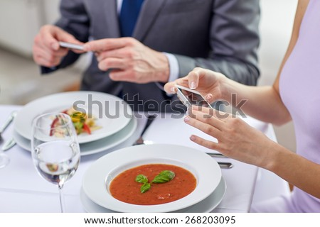 people, leisure, eating and technology concept - close up of couple with smartphones taking picture of food at restaurant - stock photo