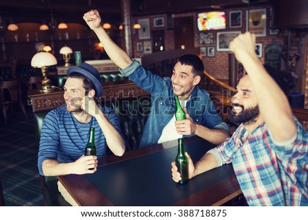 people, leisure, friendship and bachelor party concept - happy male friends drinking bottled beer and raised hands rooting for football match at bar or pub - stock photo