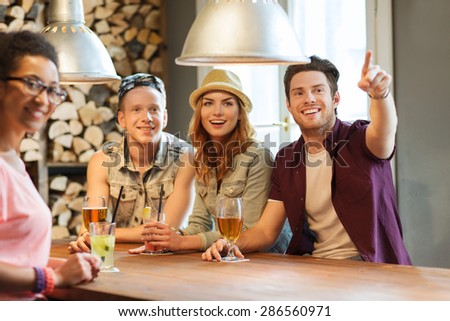 people, leisure, friendship and communication concept - group of happy smiling friends drinking beer and cocktails at bar or pub and pointing finger to something - stock photo
