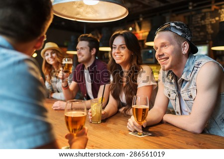 people, leisure, friendship and communication concept - group of happy smiling friends drinking beer and cocktails talking at bar or pub - stock photo