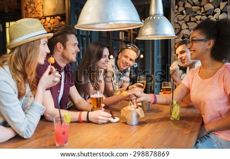people, leisure, friendship and communication concept - group of happy smiling friends drinking beer and cocktails eating and talking at bar or pub - stock photo