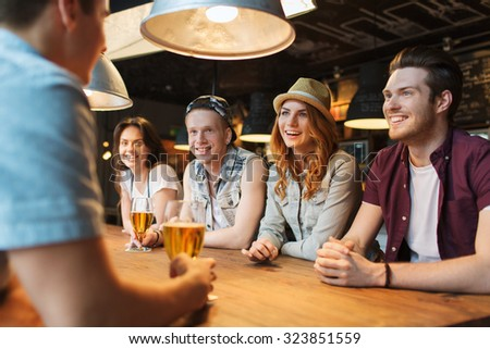 people, leisure, friendship and communication concept - group of happy smiling friends drinking beer and talking at bar or pub - stock photo