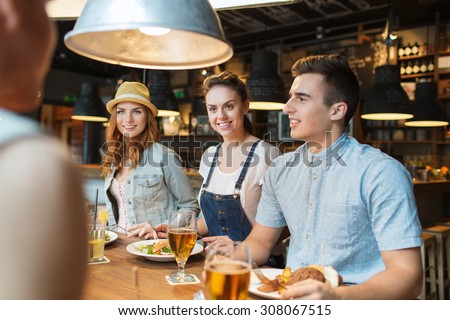people, leisure, friendship and communication concept - group of happy smiling friends eating, drinking and talking at bar or pub - stock photo