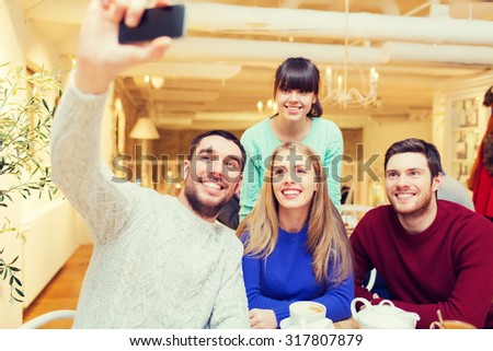 people, leisure, friendship and technology concept - group of happy friends with smartphone taking selfie and drinking tea at cafe