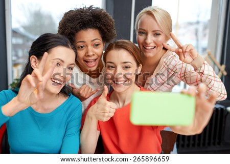 people, leisure, friendship, gesture and technology concept - happy young women taking selfie with smartphone and showing victory gesture