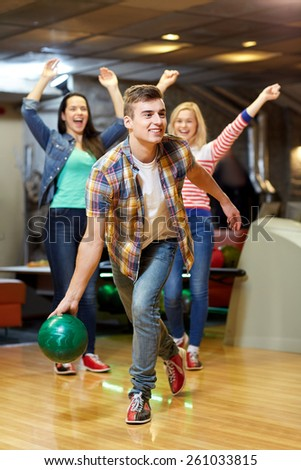 people, leisure, sport and entertainment concept - happy young man throwing ball in bowling club - stock photo