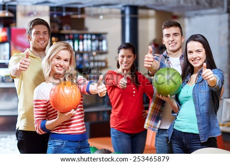 people, leisure, sport, friendship and entertainment concept - happy friends holding balls and showing thumbs up in bowling club - stock photo