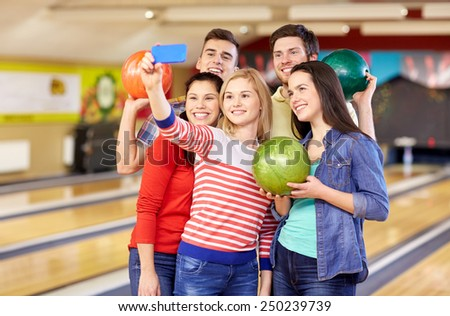 people, leisure, sport, friendship and entertainment concept - happy friends taking selfie with smartphone in bowling club - stock photo