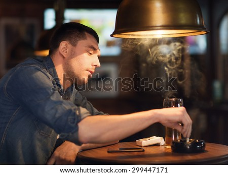 people, lifestyle and bad habits concept - man drinking beer and smoking and extinguishing his cigarette at bar or pub