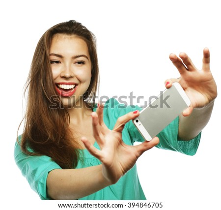 People, lifestyle and tehnology concept: pretty teen girl wearing green shirt, taking selfies with her smart phone -  isolated on white  - stock photo